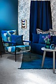 Seating area in shades of blue with armchair, sofa and side able; display case of mounted butterflies on patterned wallpaper