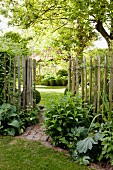 Paling fence separating beds in garden