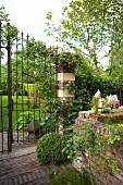 Low brick wall and open, wrought iron garden gate in mature, idyllic garden