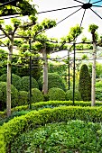 Schmiedeeiserner Pavillon mit kreisförmiger Bepflanzung verschiedener Hecken und Grünpflanzen