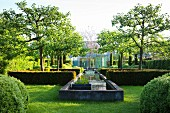 Well-tended, elegant gardens with clipped hedges and concrete pool in sunshine