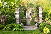 Vintage house concealed behind tall, closed garden gate and green front garden
