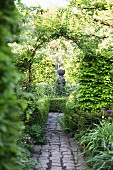 Romantic view of stone sculpture seen through climber-covered arch in lush garden