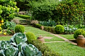 Well-tended kitchen garden with areas of lawn and grid of stone flags