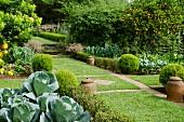 Gepflegte Nutzgartenanlage mit Rasenfläche und angeordneten Steinplatten