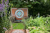 Steps paved with terracotta tiles amongst flowering perennials and back wall of stone fountain with flower-shaped pattern of glazed ceramic tiles