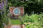 Mit Terracottafliesen belegte Treppe zwischen blühenden Stauden und Rückwand eines Natursteinbrunnens mit Blütenornament aus Keramikfliesen