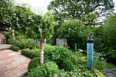 Terracotta-Terrasse, Dekosäulen und Rückwand eines Wasserbeckens mit Verzierungen aus glasierten Keramikfliesen im Hangbereich eines gepflegten Garten