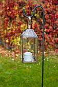 Candle lantern hanging on metal crook in garden