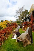 Two chairs with warm fur blankets and cushions surrounded by autumnal foliage in garden