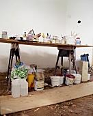 Renovierungsbedürftige Zimmerecke mit Lackdosen und Malutensilien auf langem Tapeziertisch; unter dem Tisch leere Farbeimer