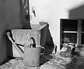 Watering can and wellington boots by water container (B&W)
