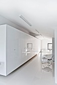 Long row of glossy, white wardrobes and 50s, tubular steel designer armchair on reflective white floor