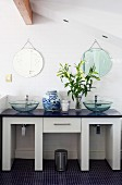 Twin washstand with glass basins and round mirrors on white, tiled wall