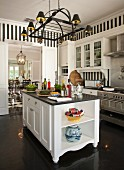 Elegant, white country-house kitchen with dark floor and black and white striped wallpaper