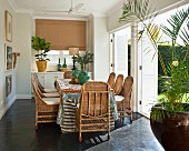 Dining area with wicker chairs and table in front of open shutters on terrace doors leading to garden
