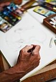 Nahaufnahme einer zeichnenden Männerhand auf Skizzenblock, Malutensilien unscharf im Hintergrund