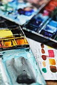 Two artist s watercolour palettes filled with paints in shades of blue and yellow