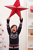 Girl holding up Christmas star, portrait