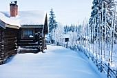 Scandinavian log cabin in snowy winter landscape