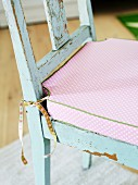 Pink seat cushion in romantic country-house style on worn kitchen chair