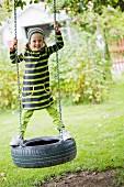 Girl on tyre swing in garden