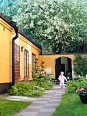 Little boy running through idyllic garden courtyard of Scandinavian bungalow