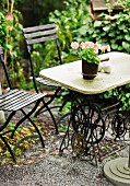 Unusual garden table made from stone table top on antique sewing machine base