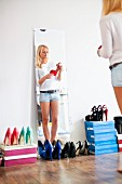 Young woman reflected in mirror selecting high-heeled shoes