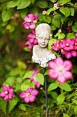 Bust of girl on metal rod amongst pink garden flowers