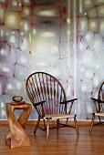 Pfauenstühle und kunstvoll gestalteter Beistelltisch aus Edelholz vor pastellfarbener Wandgestaltung