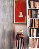 Objet d'art and antique wooden stand between exposed concrete slab and bookcase