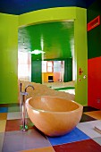 Walls and ceiling in bold shades of green and red; free-standing, oval bathtub on floor with large, square tiles in various colours
