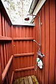 Outdoor shower with red wood panelling