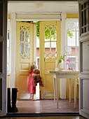 Little girl holding teddy bear looking out of open front door