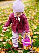 Toddler with bucket in autumnal garden