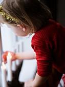 Mädchen mit Glitzerkranz im Haar betrachtet Weihnachtskerzen am Fenster