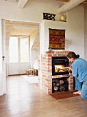Woman placing log on fire in wood-burning stove