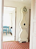 Antique, white longcase clock in tiled hallway