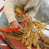 Frau bindet Strauss aus Getreideähren