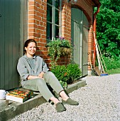 Woman with book & cup of coffee sitting on doorstep in sunny courtyard