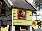 Toddler leaning out of window of wendy house in garden