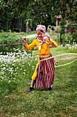 Girl wearing Swedish national dress playing with hula hoop in garden