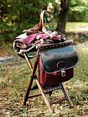 Leather bag, gloves, woollen blanket & ladies' shoes on stool in garden