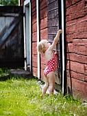Little girl in swimming costume in garden attempting to open wooden door