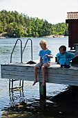 Two children sitting on wooden jetty on shore of lake playing with wooden toy boat
