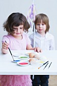 Little girl painting Easter eggs with second child watching