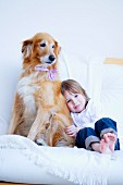 Little girl and dog on white couch