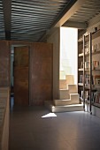 Purist library with exposed metal roof structure and cubic samba staircase flooded with sunlight
