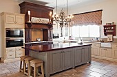 Nostalgic country-house kitchen with lit chandelier above island counter with dark, solid wood worksurface